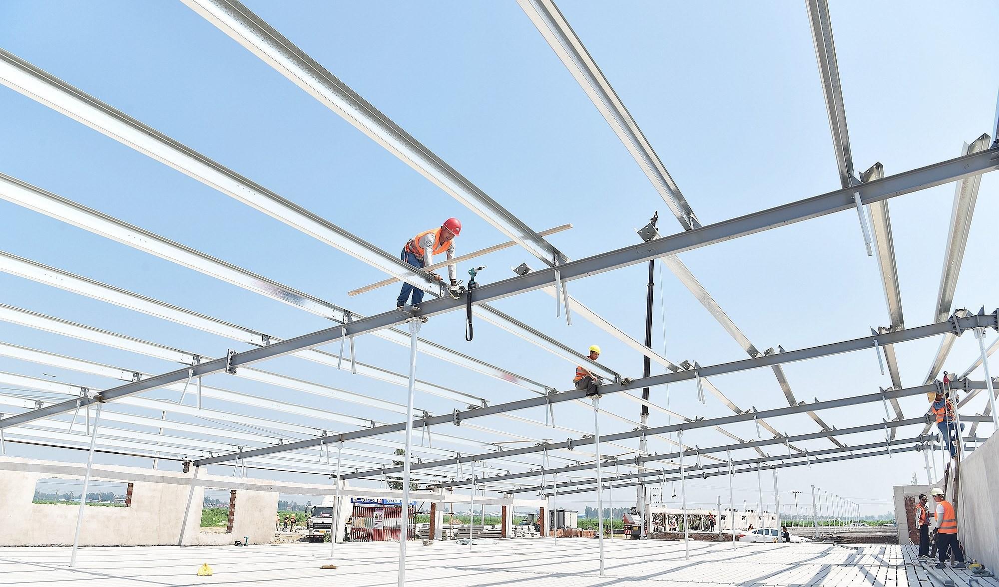 叮咛店镇西张谦村新希望集团养殖产业项目建设现场,工人正在施工